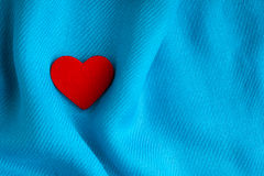 Valentine's day background. Red heart on blue folds cloth Royalty Free Stock Photography
