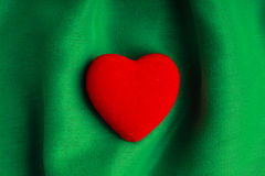 Valentine's day background. Red heart on green folds cloth Stock Photos