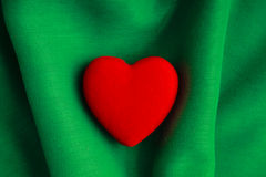 Valentine's day background. Red heart on green folds cloth. Valentine's day background. Red decorative heart on abstract green wavy folds cloth or textile Royalty Free Stock Image