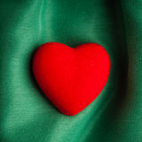Valentine's day background. Red heart on green folds cloth Stock Image