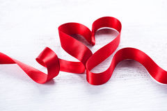 Valentine`s day background. Red heart shaped satin gift ribbon royalty free stock image