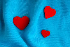 Valentine's day background. Red hearts on blue folds cloth Stock Images