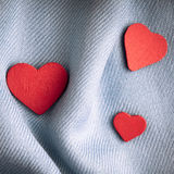 Valentine's day background. Red hearts on gray folds cloth Stock Image