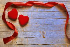 Valentine`s day background, red hearts and ribbon on old blue wooden floor Royalty Free Stock Image