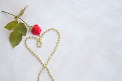 Valentine's Day background. Red rose and a heart from golden like perls. Free space for a text Royalty Free Stock Photo