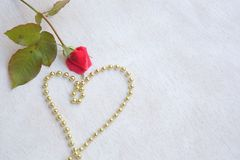 Valentine's Day background. Red rose and a heart from golden like perls. Free space for a text Royalty Free Stock Photography