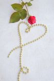 Valentine's Day background. Red rose and a heart from golden like perls on a white wooden surface. Free space for a text Royalty Free Stock Image