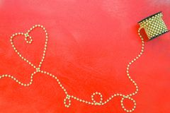 Valentine's Day background on a red wooden surface. Valentine's Day background: golden like perls in the form of a heart and a bobbin on a red wooden surface Stock Photos
