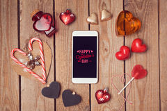 Valentine's day background with smartphone mock up and heart shapes on wooden table. Royalty Free Stock Image