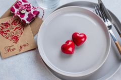Valentine`s day background table setting with two ceramic hearts on plate. Top view, copy space. Valentine`s day table setting with two ceramic hearts and gift stock photography