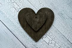 Valentine`s day background, two black vintage hearts on old wooden table stock images