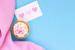 Valentine`s Day background. Valentine`s day card and cupcake with copy space on the blue background Stock Photos