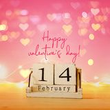 Valentine's day background. Vintage wooden calendar with 14th february date over table and pink bakground. Hearts overlay. royalty free stock photography