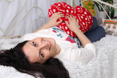 Valentine's Day. Beautiful girl lying on the bed. In the hands of the pillow heart red. The girl has dark wavy hair. Armenian. She looks happy and dreaming Stock Images