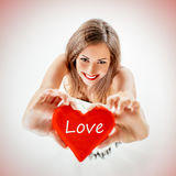 Valentine`s Day. Beautiful smiling girl holding a red heart that says Love. Looking at camera. Selective focus Stock Photography