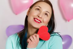 Valentine`s Day. Beautiful young woman with heart in her hands. Young woman with red heart on white background with inflatable stock photos