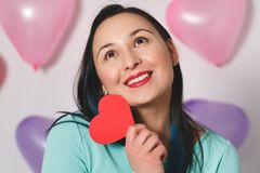 Valentine`s Day. Beautiful young woman with heart in her hands. Young woman with red heart on white background with inflatable stock photo