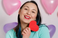 Valentine`s Day. Beautiful young woman with heart in her hands. Young woman with red heart on white background with inflatable stock images