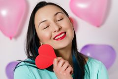 Valentine`s Day. Beautiful young woman with heart in her hands. Young woman with red heart on white background with inflatable stock photography