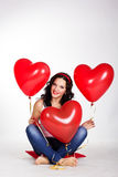 Valentine's day beautiful young woman wearing jeans and holding red balloons Royalty Free Stock Photos