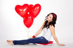 Valentine's day beautiful young woman wearing jeans and holding red balloons Royalty Free Stock Image