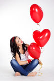 Valentine's day beautiful young woman wearing jeans and holding red balloons Stock Photos