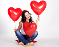 Valentine's day beautiful young woman wearing jeans and holding red balloons Stock Photography