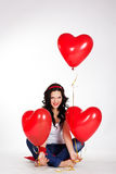 Valentine's day beautiful young woman wearing jeans and holding red balloons Royalty Free Stock Photo