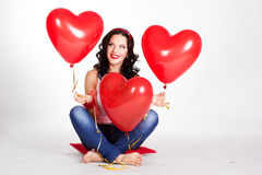 Valentine's day beautiful young woman wearing jeans and holding red balloons Royalty Free Stock Photography
