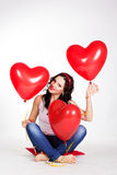 Valentine's day beautiful young woman wearing jeans and holding red balloons Stock Image