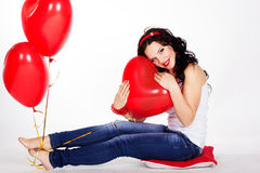 Valentine's day beautiful young woman wearing red dress and holding red balloons Royalty Free Stock Images