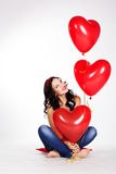 Valentine's day beautiful young woman wearing red dress and holding red balloons Royalty Free Stock Photo