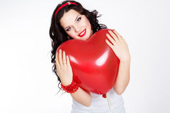 Valentine's day beautiful young woman wearing red dress and holding red balloons Royalty Free Stock Image