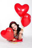 Valentine's day beautiful young woman wearing red dress and holding red balloons Royalty Free Stock Photography