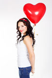 Valentine's day beautiful young woman wearing red dress and holding red balloons Stock Images