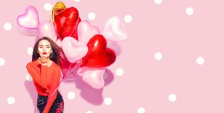Valentine`s Day. Beauty girl with colorful air balloons having fun over pink background royalty free stock photo