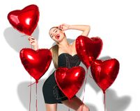 Valentine`s Day. Beauty girl with red heart shaped air balloons having fun, isolated on white Stock Photography