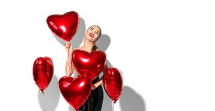 Valentine`s Day. Beauty girl with red heart shaped air balloons having fun, isolated on white Royalty Free Stock Images
