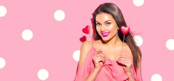 Valentine`s Day. Beauty surprised young fashion model girl with Valentine heart shaped cookies. Isolated on pink background royalty free stock photo