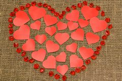 ..Valentine`s day. Big red heart made of little hearts lying on a brown bag around it are red crystals. Valentine`s day. Big red heart made of little hearts stock photos