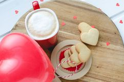 Valentine`s Day, biscuits and balloon-shaped heart and cup of co royalty free stock images