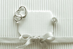 Valentine`s day, black and white image. Silk ribbon, silver heart pendant, two, little rose on grooved paper Royalty Free Stock Image