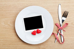 Valentine's Day blank photo frame over plate and silverware Royalty Free Stock Images