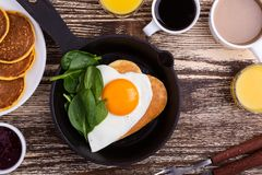Valentine`s day breakfast or brunch with heart shape fried egg. Valentine`s day breakfast or brunch. Homemade heart shape fried egg and pancake in cast iron stock photography