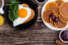 Valentine`s day breakfast with heart shape fried egg in cast ir. Valentine`s day breakfast or brunch. Homemade heart shape fried egg and pancake in cast iron stock image