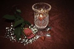 Valentine`s Day candlelight and single red rose. Single red rose and heart shaped chocolates. Candlelight from crystal hurricane lamp royalty free stock photos