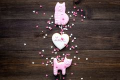 Valentine`s Day candy. Heart shaped cookie with lettering Love and kitty on dark wooden background top view space for. Valentine`s Day candy. Heart shaped cookie Royalty Free Stock Image