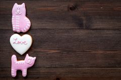 Valentine`s Day candy. Heart shaped cookie with lettering Love and kitty on dark wooden background top view space for. Valentine`s Day candy. Heart shaped cookie Stock Image