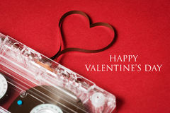 Valentine's day card. Audio cassette with magnetic tape in shape of heart on red background Royalty Free Stock Photography
