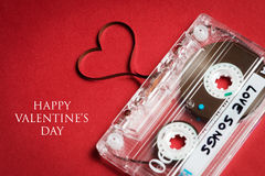 Valentine's day card. Audio cassette with magnetic tape in shape of heart on red background Stock Photography